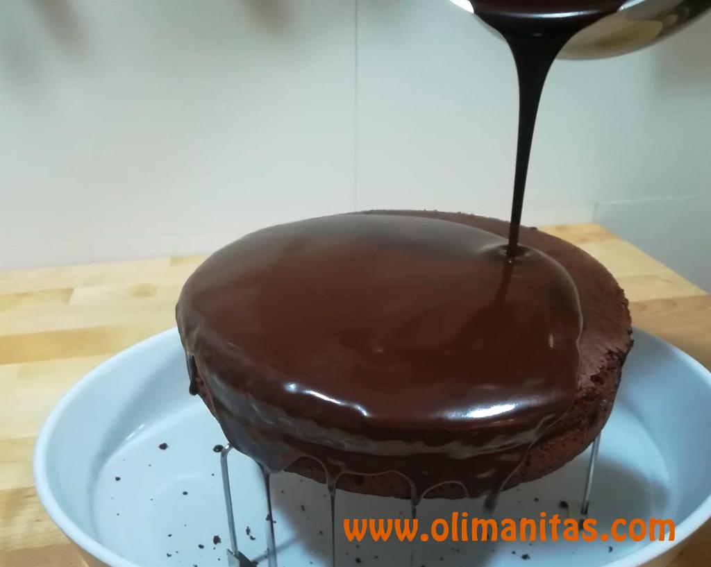 Cuando veamos que el chocolate tiene la textura correcta; lo vertemos sobre el bizcocho de una vez y dejamos que él solo vaya cubriendo todas las partes formando así el clásico glaseado de la tarta Sacher.